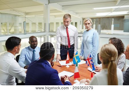Young and mature politicians standing by table and listening to their foreign colleagues during discussion of strategies