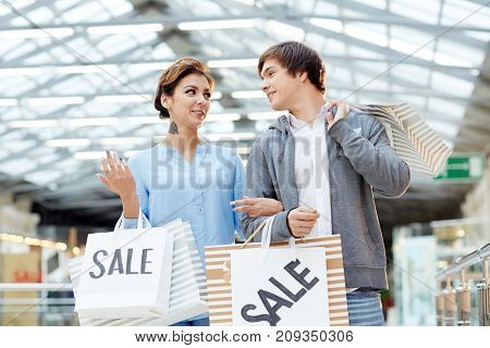 Happy young amorous couple with paperbags visiting modern mall in period of seasonal sale and hot offers
