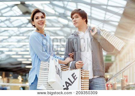 Young affectionate couple visiting traditional xmas sale in large mall
