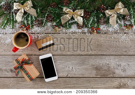 Preparing for winter holidays background. Smartphone, credit card, coffee cup and christmas gift on wooden table. Seasonal sales, online shopping. Top view, flat lay, copy space