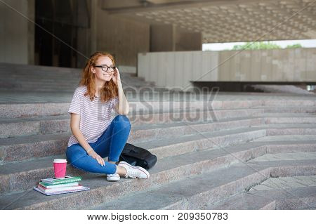 Happy redhead girl in glasses talking on mobile, sitting on the stairs outdoors at university campus. Communication and education concept