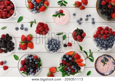 Healthy breakfast background and pattern. Light greek yogurt, fresh strawberries, raspberries, blueberries and blackberries frame on white wood. Detox and eating right concept, top view