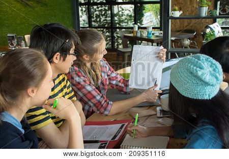 Group of teenage friends working and meeting in team with reports on wooden table