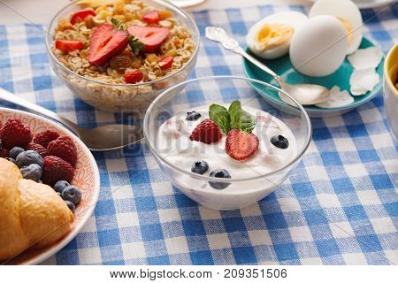 Rich continental breakfast menu. French crusty croissants, muesli, yogurt and boiled eggs for tasty morning meals on checkered tablecloth