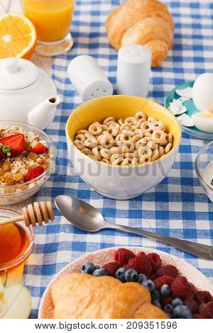 Rich continental breakfast menu. French crusty croissants, muesli, teapot, yogurt for tasty morning meals on checkered tablecloth