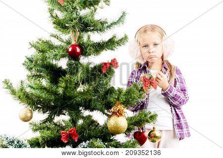 Studio portrait of little girl decorating Christmas tree