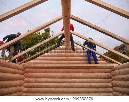 CLUJ-NAPOCA ROMANIA - OCTOBER 13 2017: New log cabin interior. Carpenters assemble timber frame with common rafters on cabin roof in the evening
