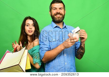 Man With Beard Holds Credit Card And Piggy Bank