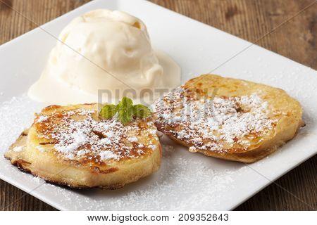 austrian apfelkuechle with vanilla ice cream on wood
