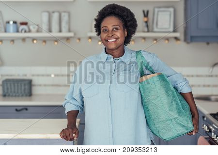 Smiling young African woman standing alone in her kitchen at home holding a shopping bag of fresh produce