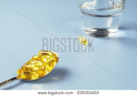 Capsules of fish oil in spoon and glass with water on blue table. Space for your text