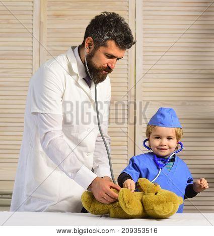 Vet And Little Assistant Examine Teddy Bear.