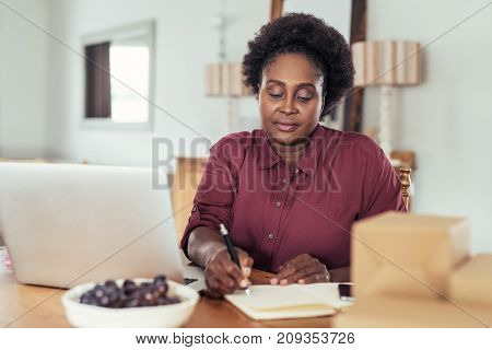 Focused young African woman sitting at her kitchen table writing in a notebook and using a laptop while working from home