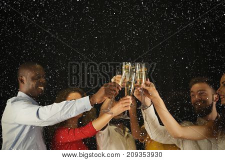 Christmas party time. Young people toasting with champagne flutes. Multiethnic friends congratulating each other with new year. Celebration and nightlife concept, holiday background, selective focus