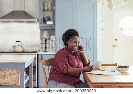 Smiling young African woman using a digital tablet and talking on a cellphone while sitting at her kitchen table working from home