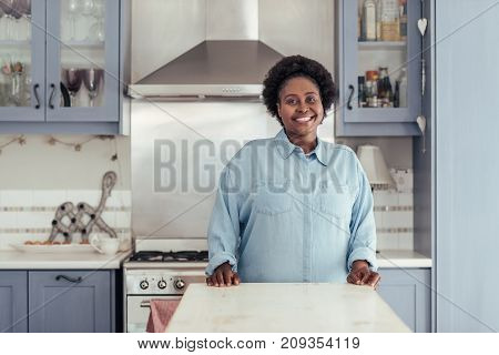 Content young African woman smiling while standing alone at a counter in her kitchen at home