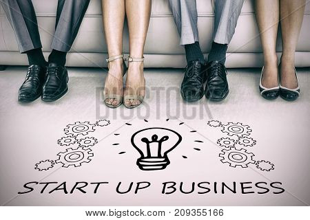 Digital image of light bulb amidst gears over start up business text against low section of executives waiting for interview