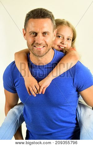 Schoolgirl Sits On Dads Back. Daughter And Father Hug