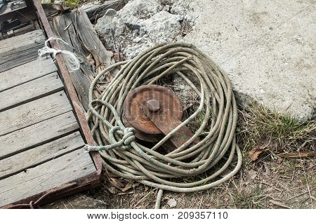 Old rusty weathered iron reel with used wound rope on grunge background