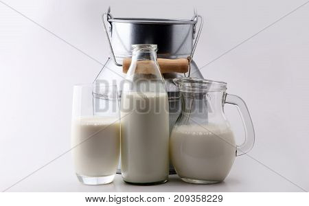 A jug of milk and glass of milk on white background.