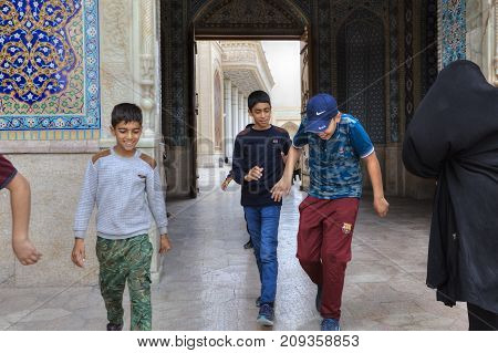 Fars Province Shiraz Iran - 19 april 2017: Shah Cheragh Shrine Iranian teenagers boys pass through the large gate of mosque Iran.