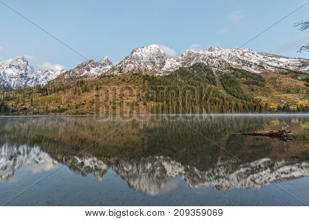 a reflection of the Tetons at sunrise in fall in String Lake