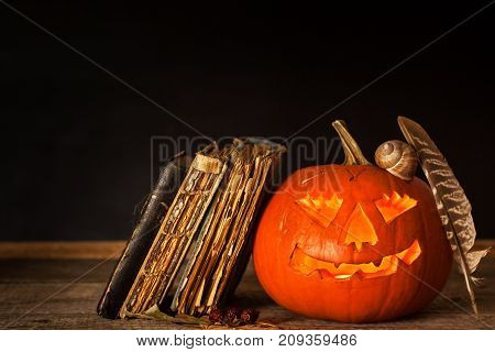 Halloween pumpkin and a book of spells. Carved pumpkin. Magic books. Traditional holiday