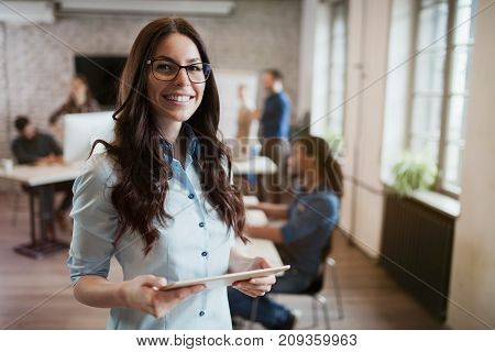 Portrait of young beautiful female designer holding tablet in office