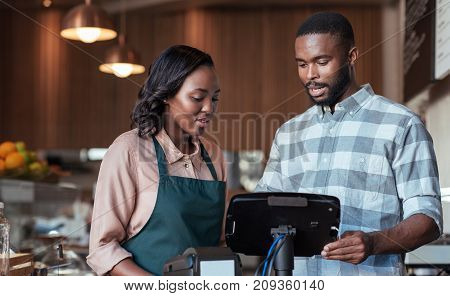 Two young African entrepreneurs working together on the terminal at the checkout counter of their bistro