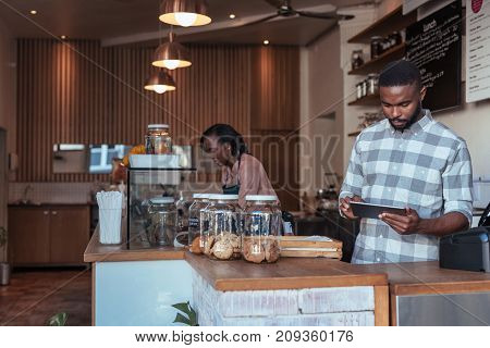 Young African entrepreneur standing behind his cafe counter using a digital tablet with a colleague working in the background