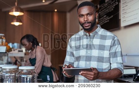 Portrait of a young African entrepreneur standing behind his cafe counter using a digital tablet with a colleague working in the background