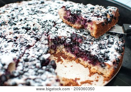 Sliced Powdered Blackcurrant Tart On A Round Baking Tray