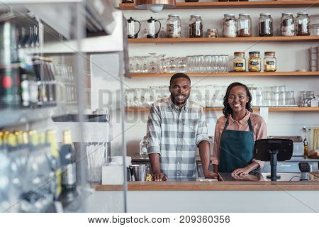 Portrait of two successful young African entrepreneurs standing together behind the counter of their trendy cafe