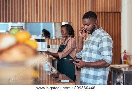Young African entrepreneur standing behind his cafe counter talking on a cellphone and using a digital tablet with a colleague working in the background