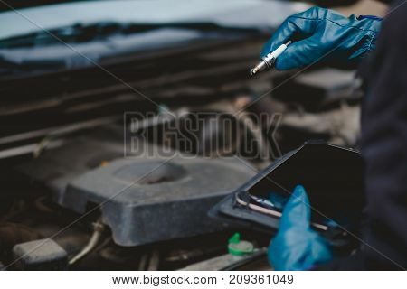 Automechanic conducts diagnostics of the spark plug machine using a tablet computer