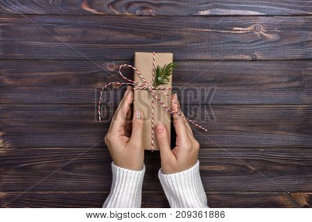 Female hands wrapping christmas gift box above wooden table. Top view.