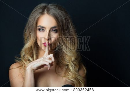 portrait of beautiful young girl with makeup and hairdress on head on black background gesture shows silence