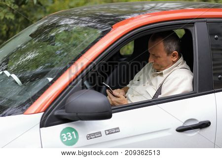 MOSCOW - SEP 17, 2017: Elderly man (wirh MR) in Smart car for carsharing, сarshring is kind of short-term car rental. Carriage allows you to return car at any of points of service