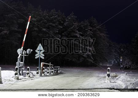 railway crossing in winter at night in forest