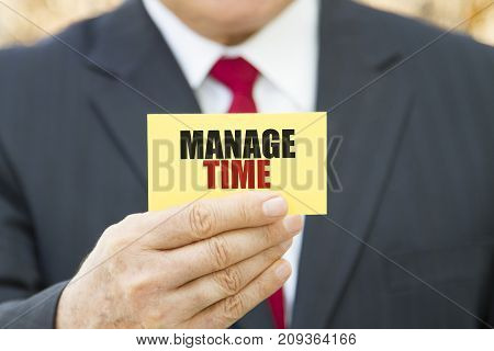 Businessman showing a card with text MANAGE TIME.