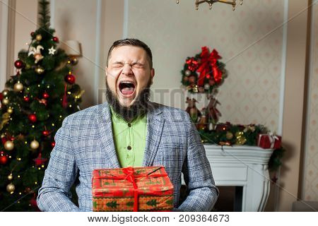 man with beard yawns and gives red box with a gift on the background of Christmas tree. concept of modern Santa