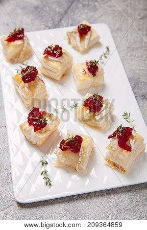 Holiday appetizers with cranberry sauce, brie cheese and thyme