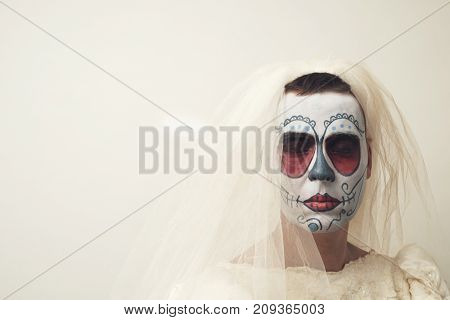 closeup of a person with short hair in a bride dress with a mexican calaveras makeup, wearing veil, against an off-white background with a blank space on the left