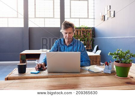 Smiling mature businessman sitting alone at his desk in a large modern office working online with a laptop