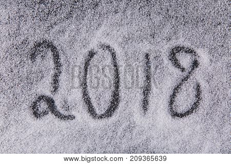 Written by a finger number 2018 on the texture of white sugar crystals on the black background