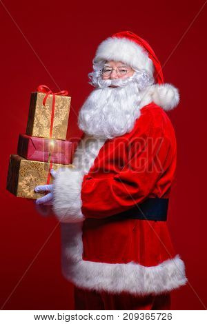 Christmas and New Year concept. Portrait of good old Santa Claus holding gifts. Red background.