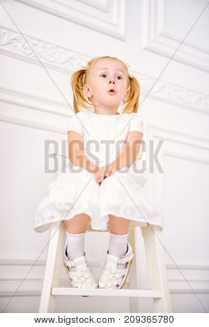 Cute two year old girl in white dress sits in a white room. Happy childhood.