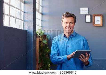 Portrait of a smiling mature businessman standing alone by windows in a large modern office working online with a digital tablet