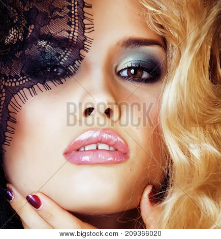 Portrait of beauty blond young woman through black lace close up sensual seduction, hairstyle waves