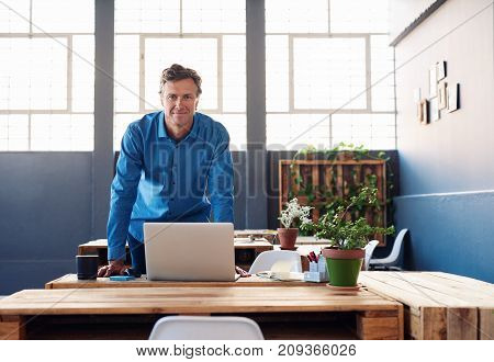 Portrait of a smiling businessman leaning confidently over a laptop on his desk in a large modern office working online with a laptop